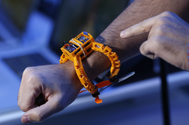 An attendee wears a prototype Nixie camera drone during the International CES Thursday, Jan. 8, 2015, in Las Vegas. The small drone, designed to be worn on the wrist, can be thrown into the air and automatically take a picture or video clip of the user. (AP Photo/John Locher)